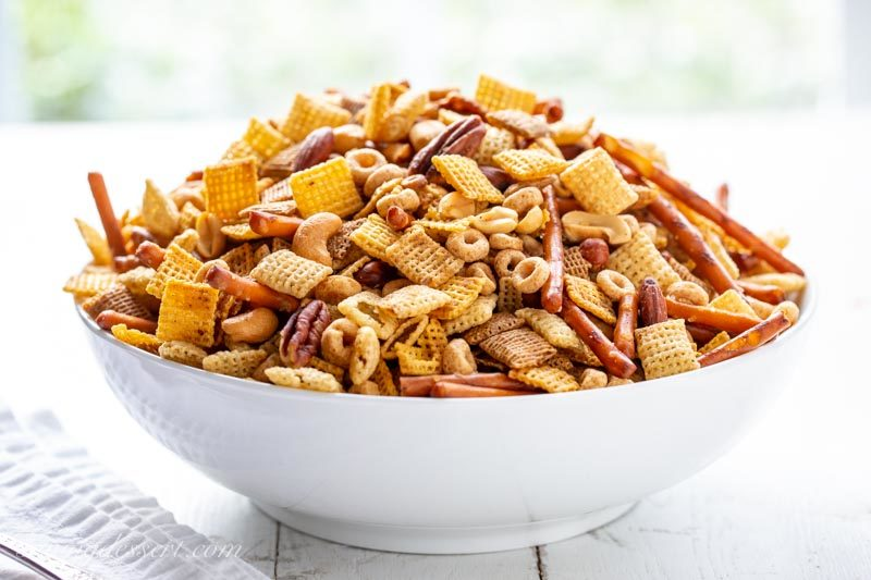 A big bowl of Party Chex Mix with Chex cereal, pretzel sticks, assorted nuts and Cheerios