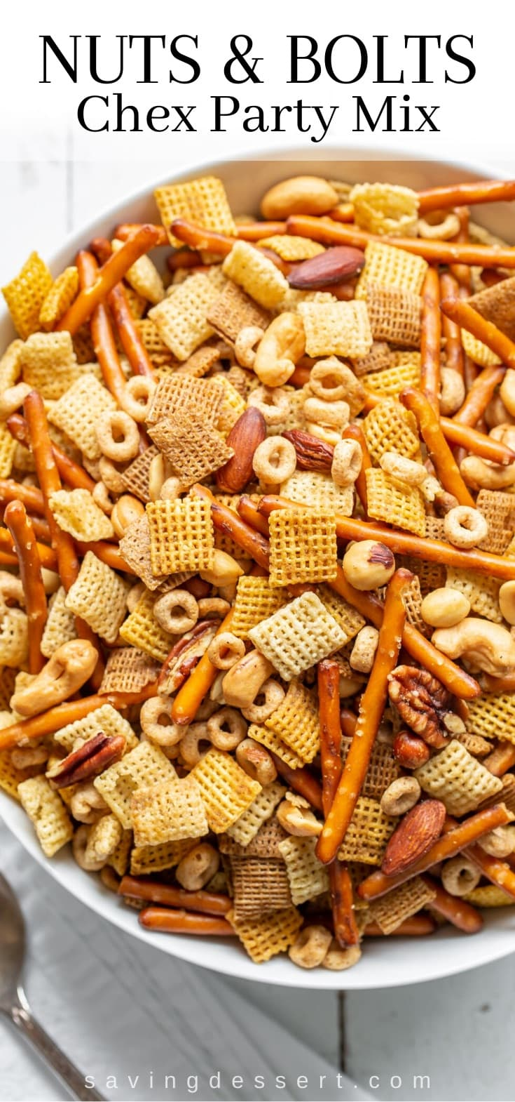 A big bowl of chex party mix with pretzels, cereal and nuts
