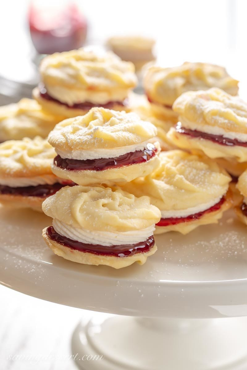 A cake plate stacked with Viennese Whirls, butter cookies piped into swirls sandwiched together with raspberry jam and buttercream