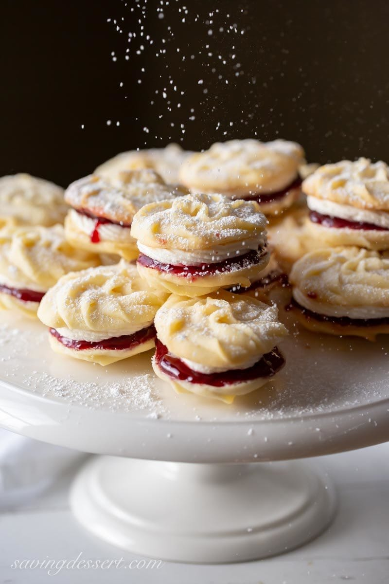 A platter of Viennese Whirls, little butter cookies piped into swirls sandwiched together with jam and buttercream and dusted with powdered sugar