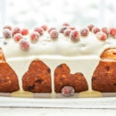 A side view of a loaf of cranberry orange bread topped with a dripping icing and sugared cranberries