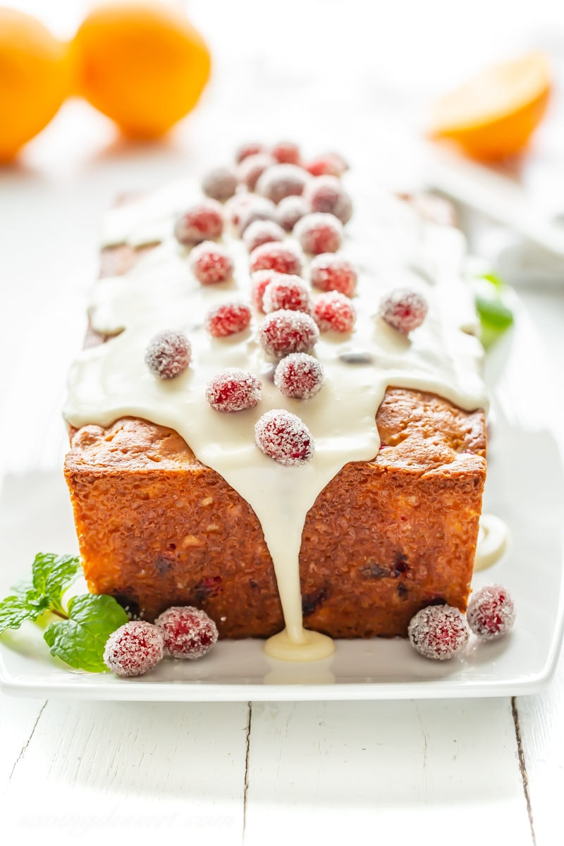 A loaf of cranberry orange bread with an orange icing and sugared cranberries on top