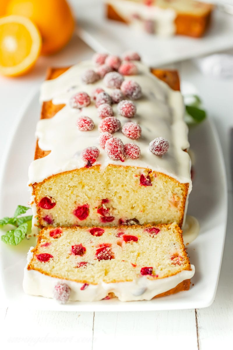 a sliced loaf of cranberry orange bread topped with sugared cranberries