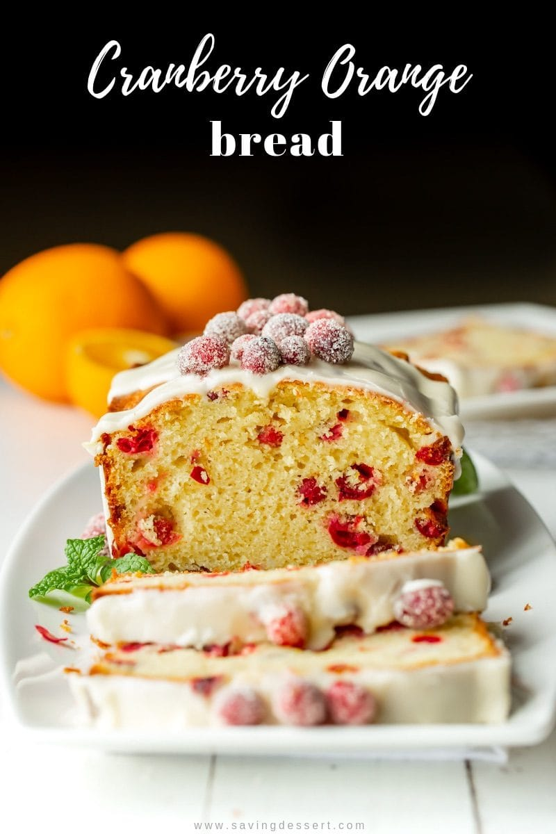 A sliced Cranberry Orange Bread with an orange glaze icing and sugared cranberries on top