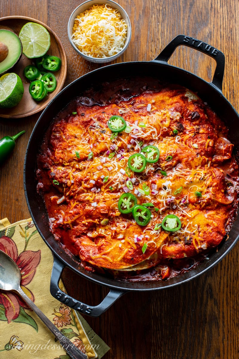 A skillet with chicken enchiladas topped with sliced jalapeño peppers, onions and cheese.
