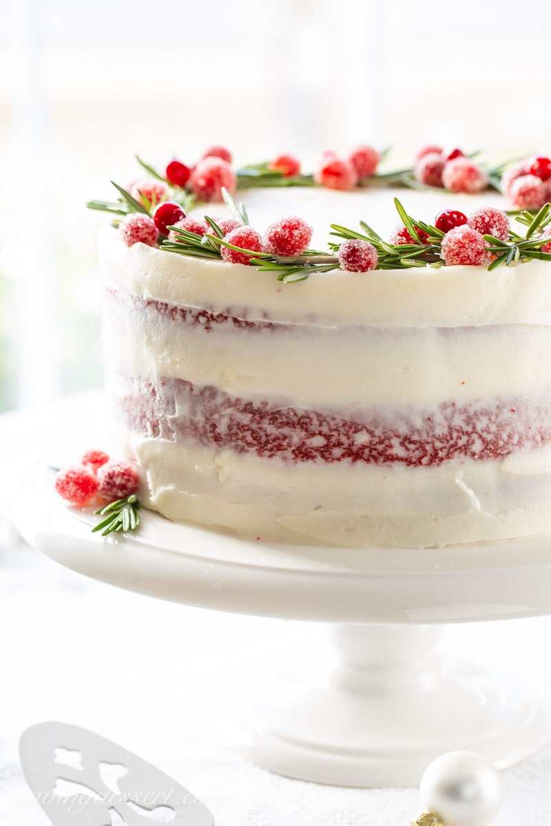 Red Velvet Layer Cake with Rosemary and sugared cranberries on top forming a wreath