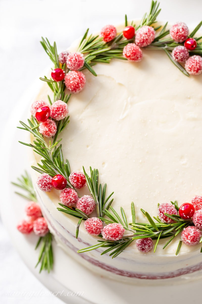 A red velvet layer cake with a wreath made of rosemary sprigs and sugared cranberries.