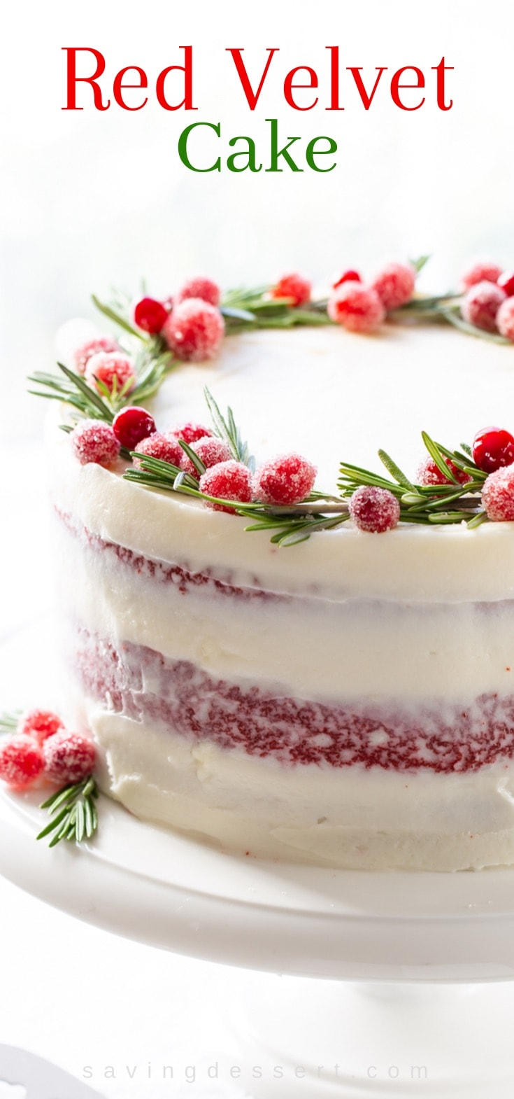 A three layer red velvet cake topped with sugared cranberries and fresh rosemary