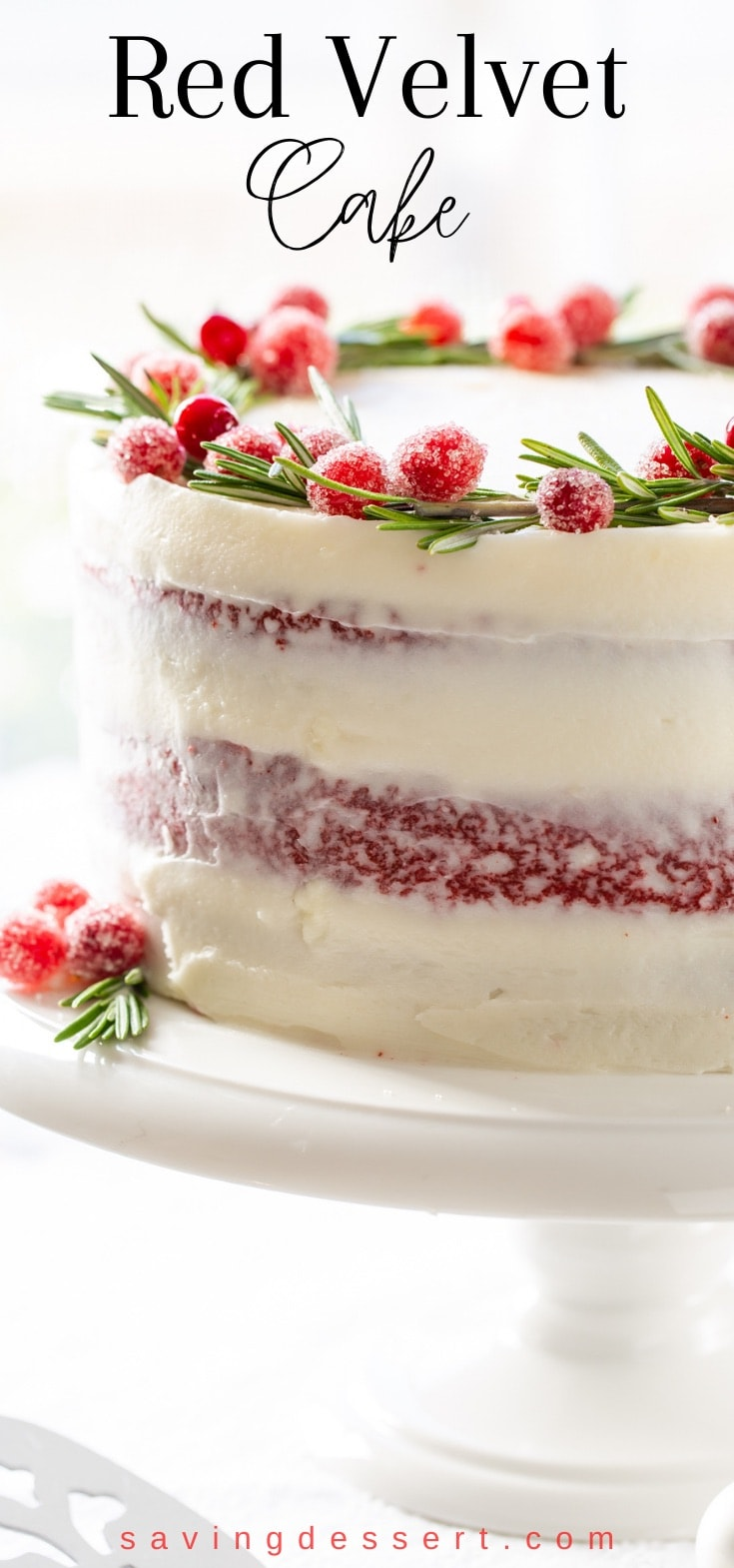 A side view of a naked Red Velvet Cake with cream cheese frosting and sugared cranberries