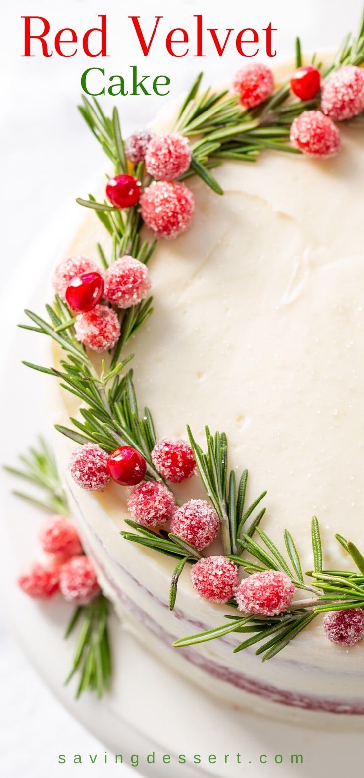 Red velvet cake topped with sugared cranberries and rosemary