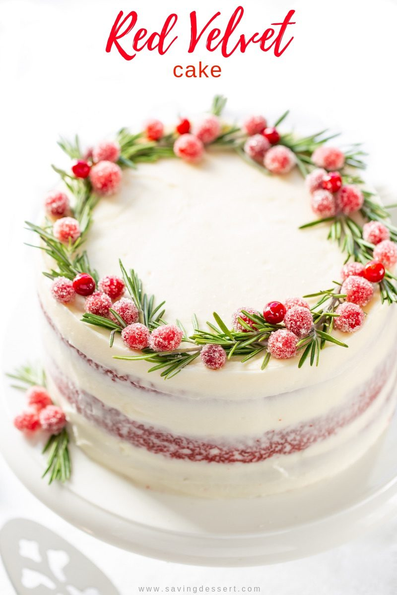 Red Velvet Layer Cake with a wreath on top made of sugared cranberries and rosemary sprigs