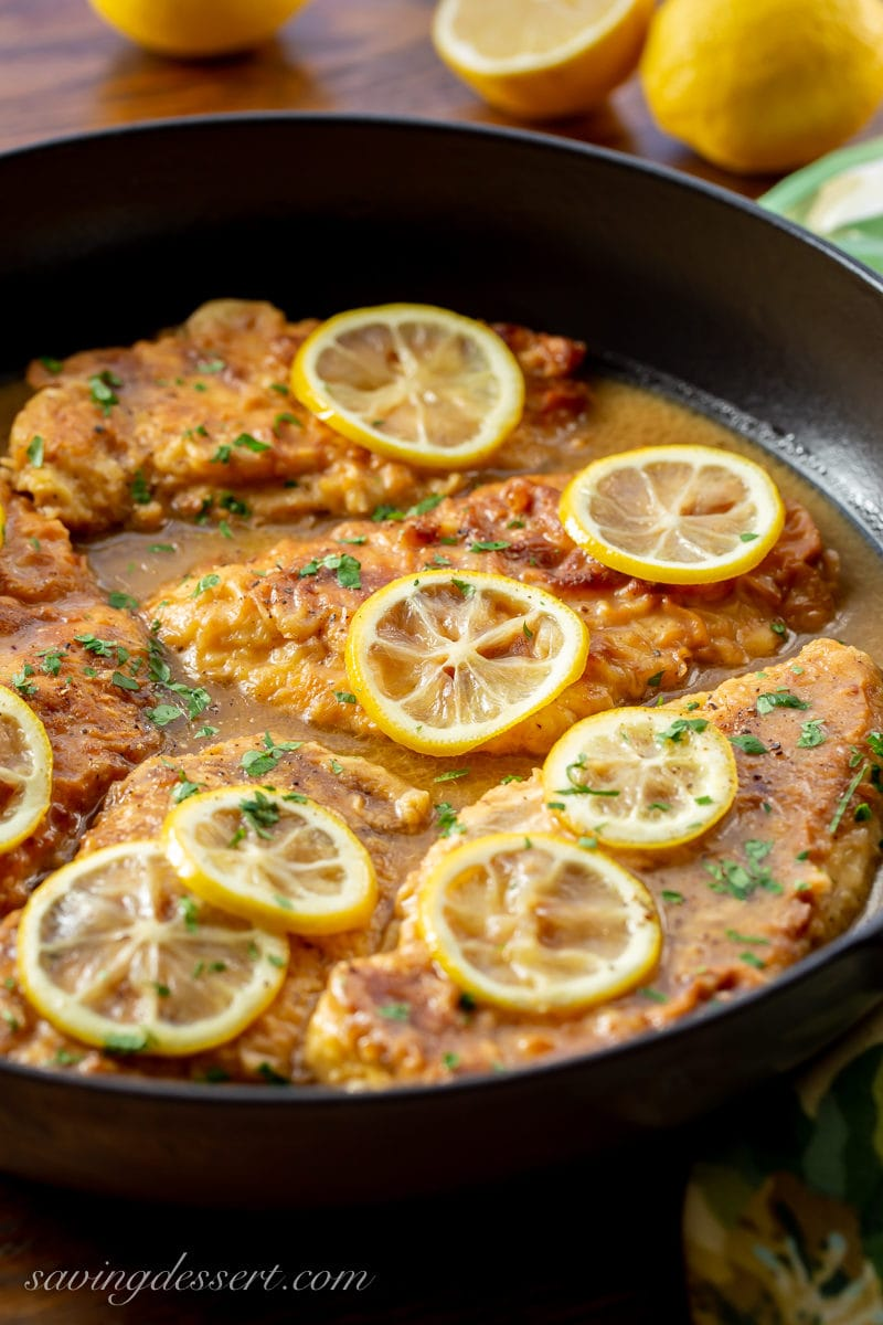 Chicken Francese - a skillet with tender, breaded chicken cutlets in a simple buttery, lemon sauce. Garnished with sliced lemons and fresh chopped parsley