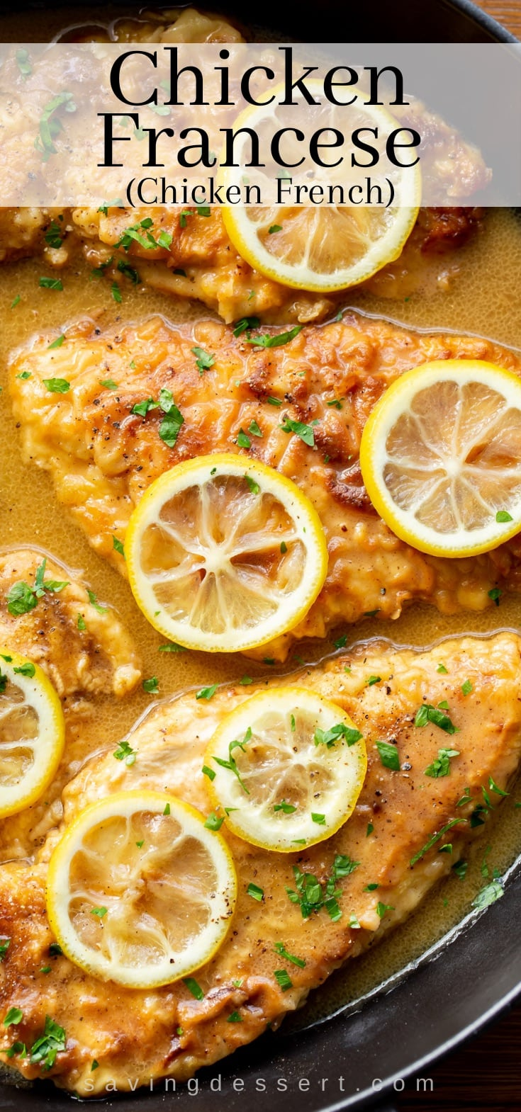A skillet with lighted breaded chicken breasts with lemon