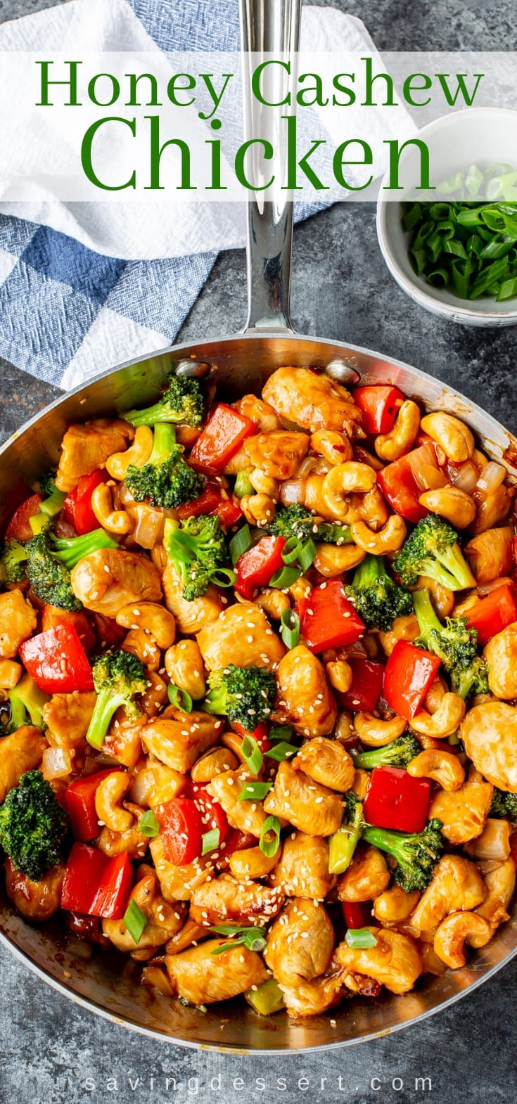 A skillet filled with honey cashew chicken with broccoli, red peppers and sesame seeds