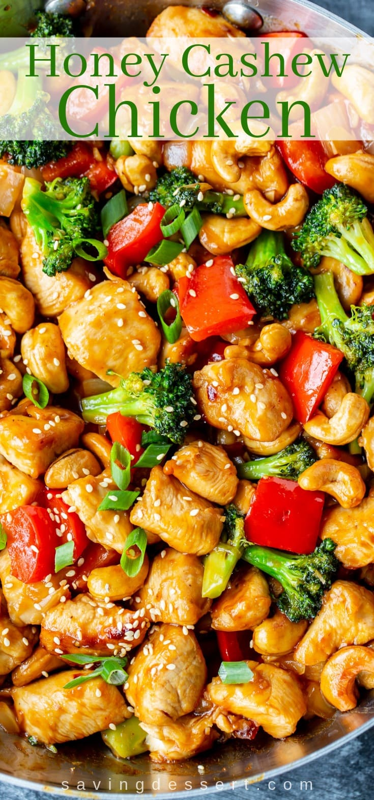 A skillet loaded with honey cashew chicken with red bell pepper and broccoli