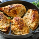 A skillet filled with Oven-Roasted Greek Chicken Breasts