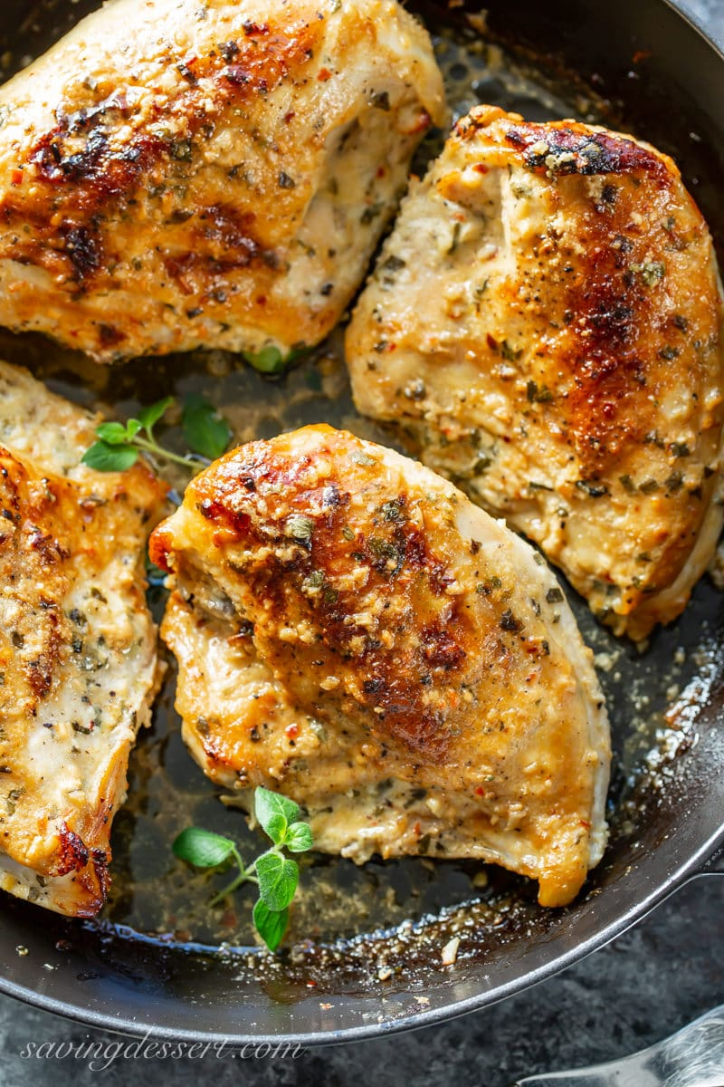 Juicy, plump, golden brown oven roasted chicken breasts in a pan with herbs and garlic.