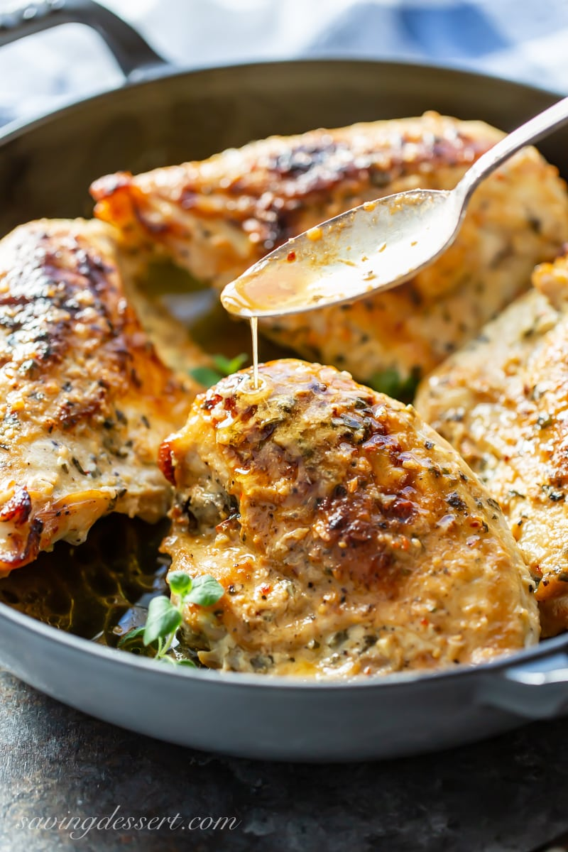 A skillet with bone-in, skin-on chicken breasts in a garlic, lemon butter sauce