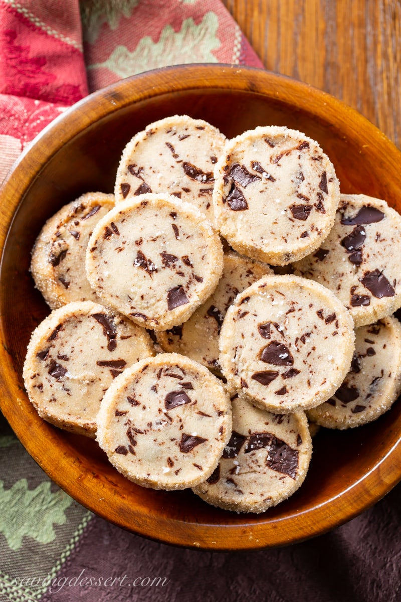 A wooden bowl filled with chocolate chunk shortbread cookies with sea salt