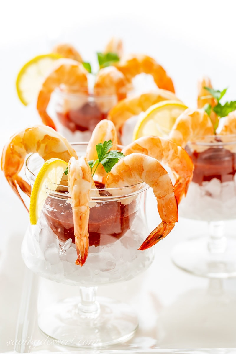 Individual glasses of shrimp cocktail with cocktail sauce and lemon slices