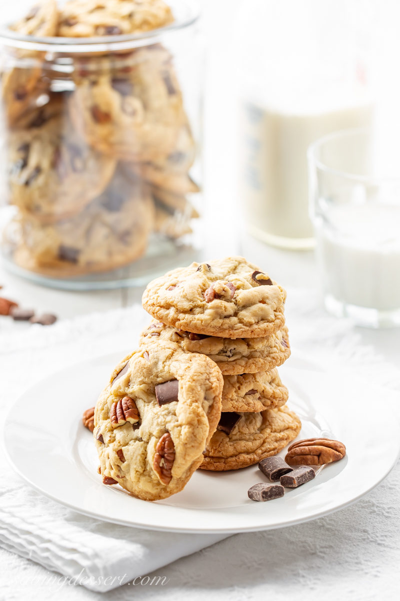 A stack of thick and chewy chocolate chunk cookies with pecans and a glass of milk