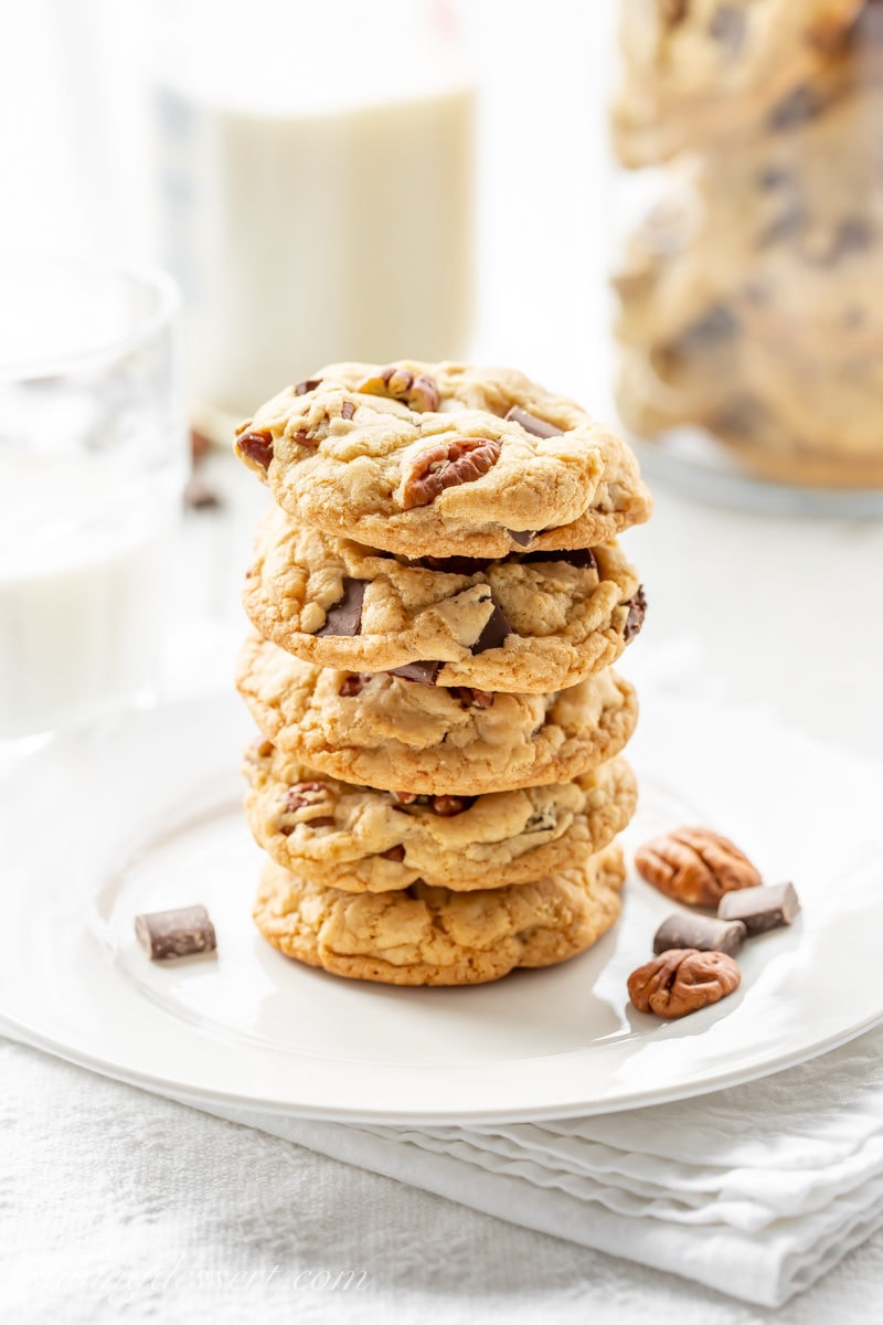A stack of chocolate chunk cookies with pecans and a bottle of milk