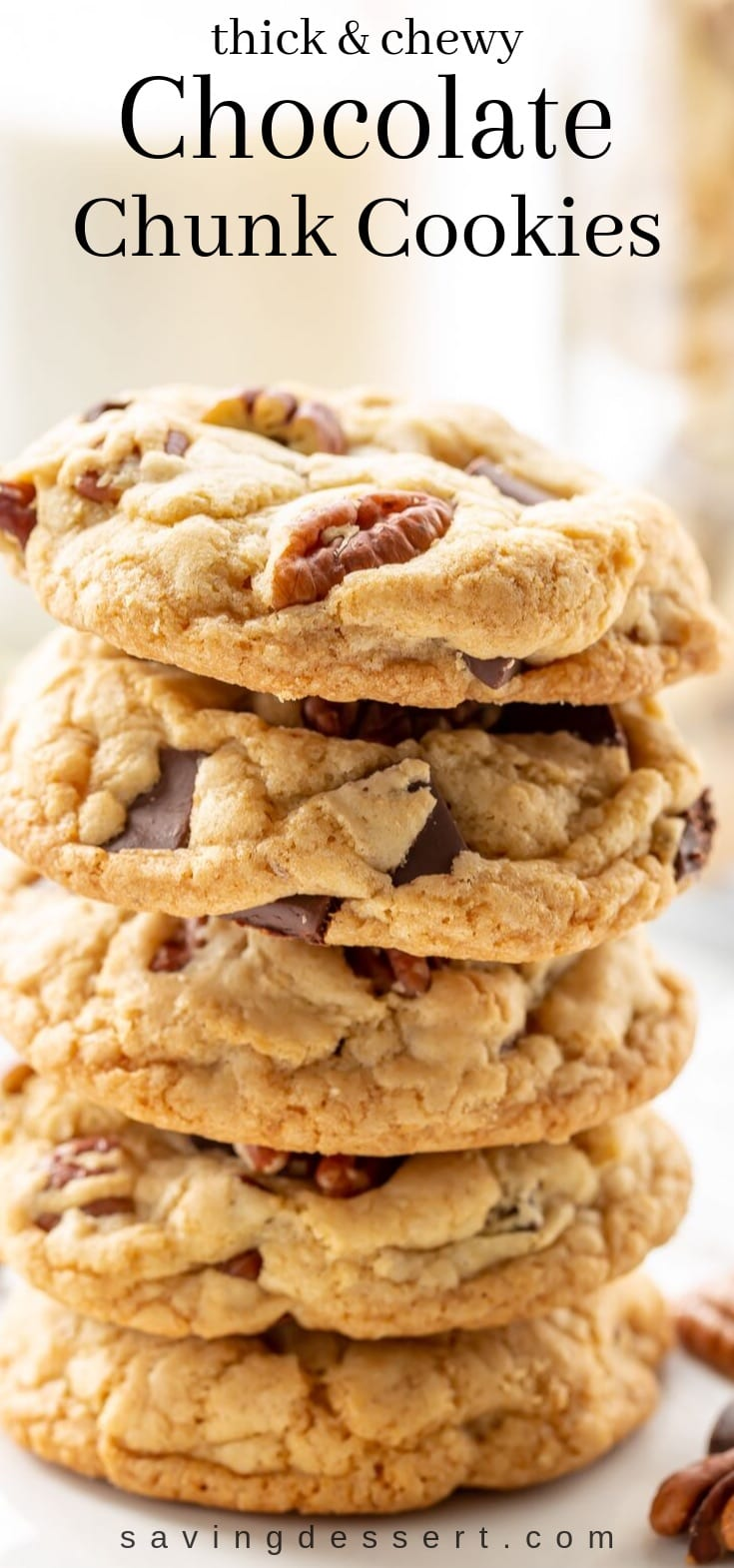 A stack of thick and chewy chocolate chunk cookies with pecans