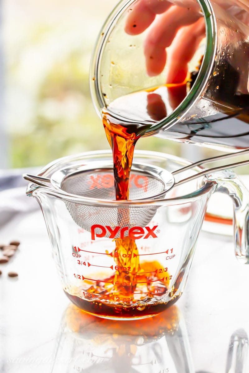 Coffee extract poured through a fine mesh sieve to remove coffee beans
