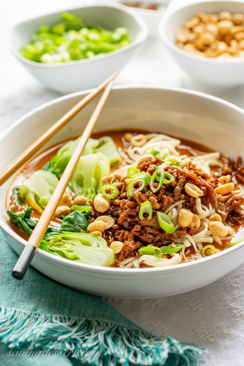 A big bowl of spicy Dan Dan Noodles with minced pork, bok choy and a rich peanut sauce garnished with peanuts and sliced green onions.
