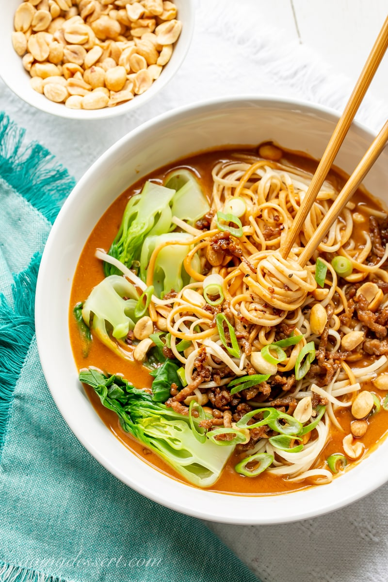 Dan Dan Noodles in a bowl with bok choy and peanuts