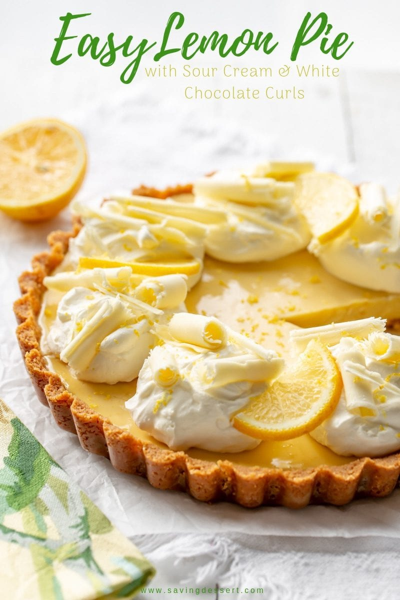 A creamy lemon tart with mounds of whipped cream, sliced lemons and white chocolate curls