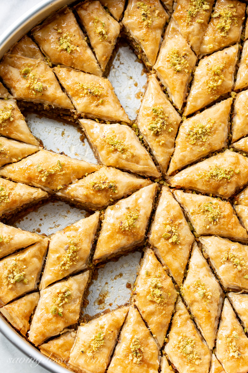 A round pan with Honey Pistachio Baklava cut into diamond shaped wedges