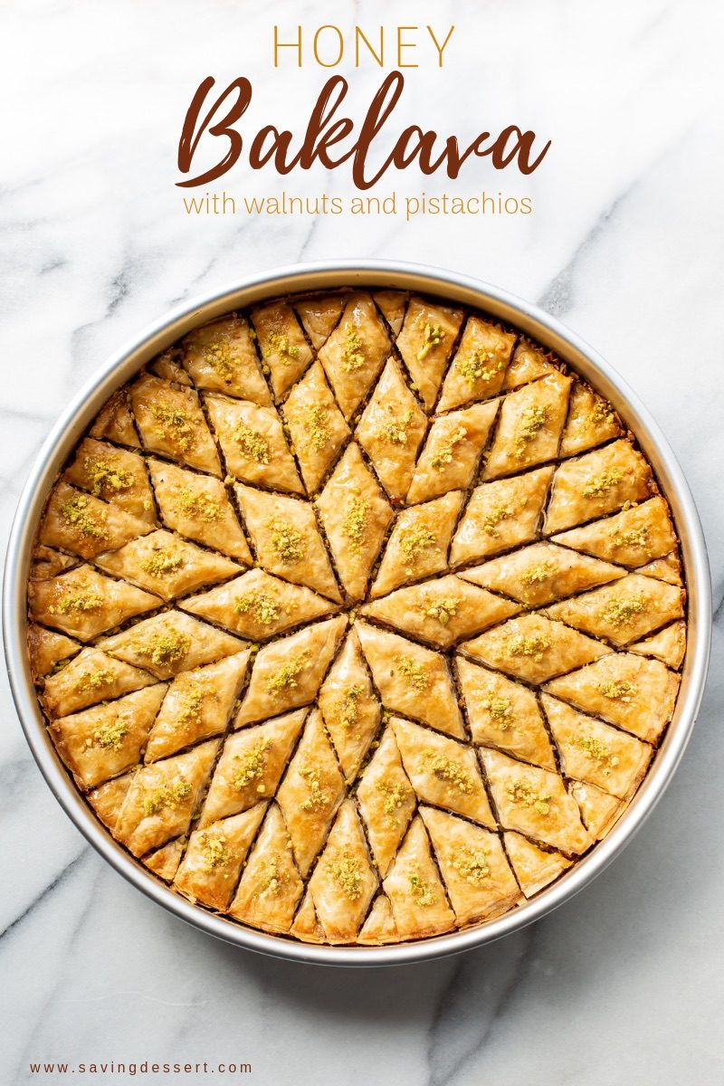 A round baking pan filled with honey soaked baklava with pistachios cut into a diamond pattern.