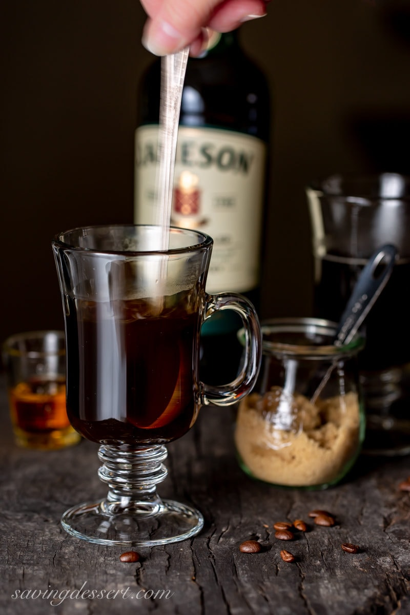 Stirring hot coffee in a clear mug as part of an Irish Coffee recipe