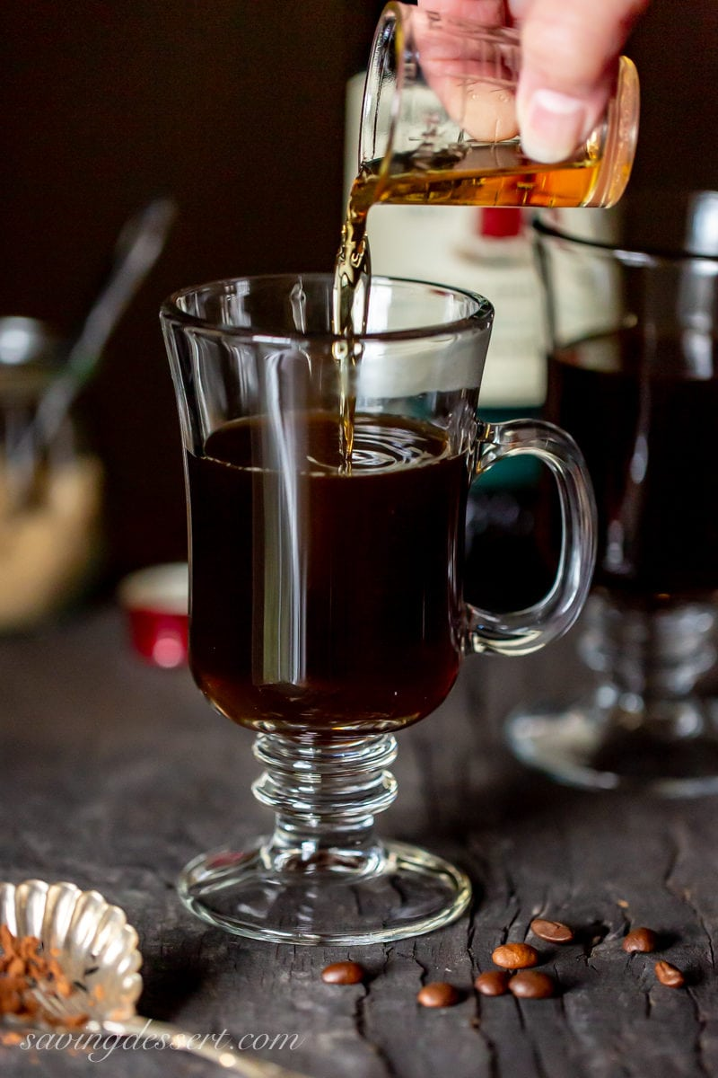Pouring Irish whiskey into a clear mug with coffee