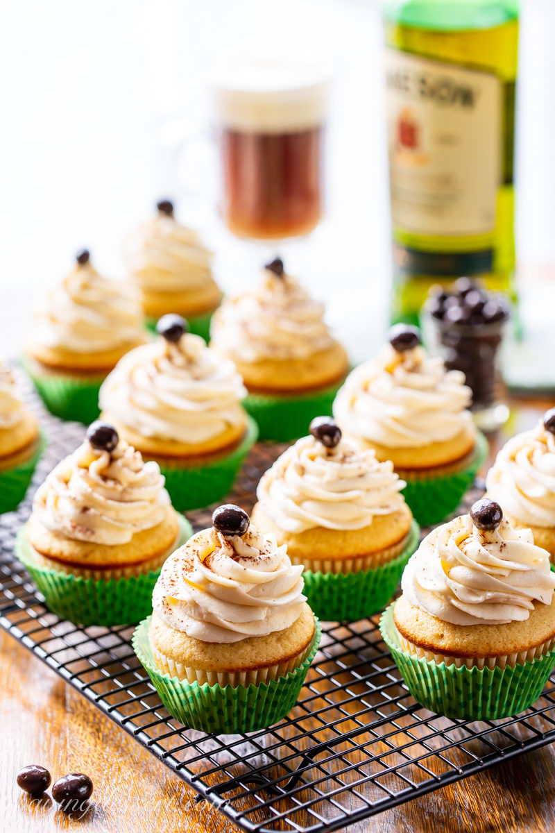 A cooling rack filled with Irish Coffee Cupcakes with swirled frosting topped with a chocolate covered espresso bean