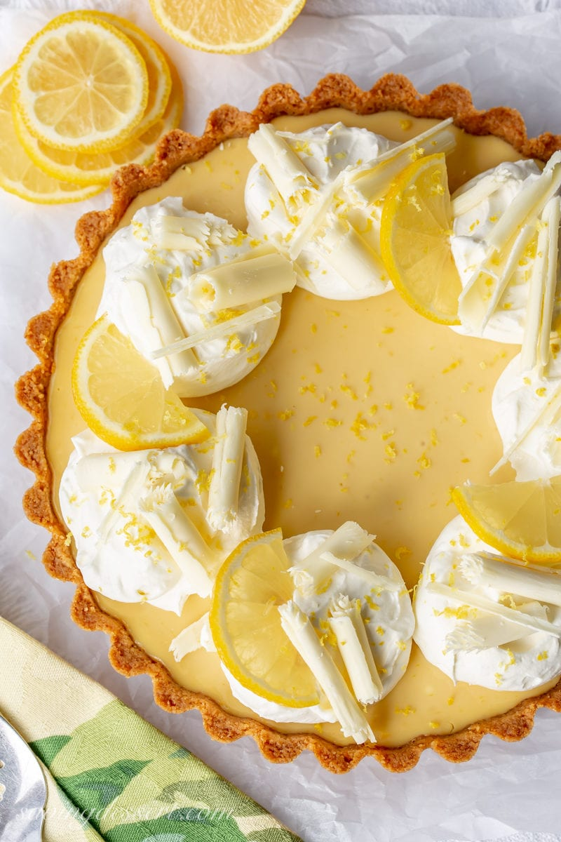 An overhead view of a lemon tart with mounds of whipped cream, lemon slices and chocolate curls.