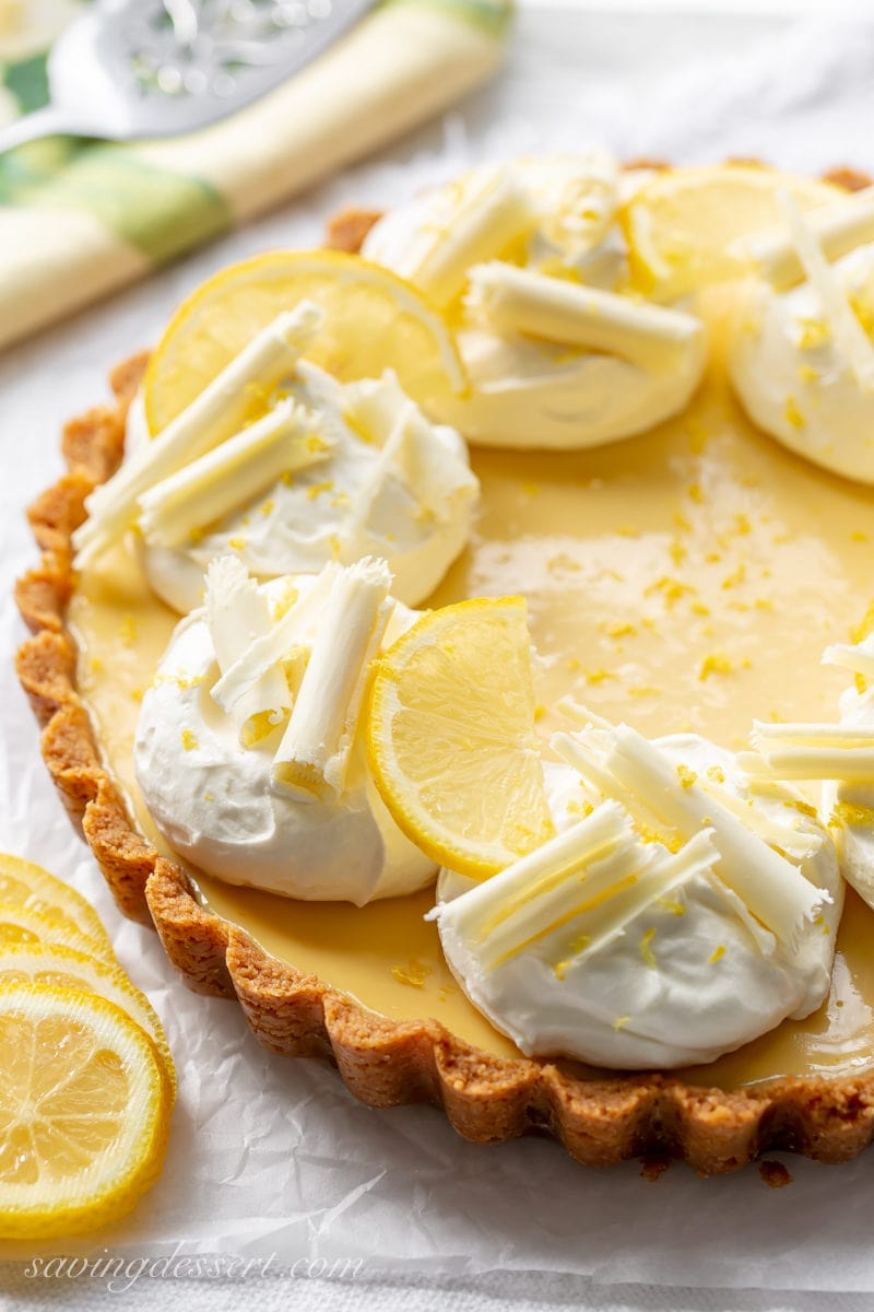 A lemon tart with graham cracker crust, mounds of whipped cream and chocolate curls