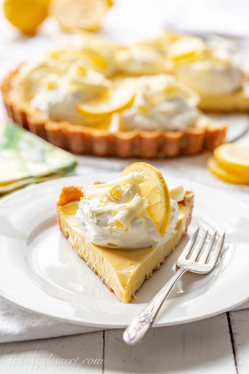 A slice of lemon pie with a mound of whipped cream, sliced lemon and white chocolate curls.