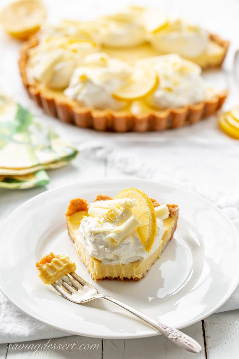 A slice of lemon pie topped with whipped cream, white chocolate curls and a slice of lemon