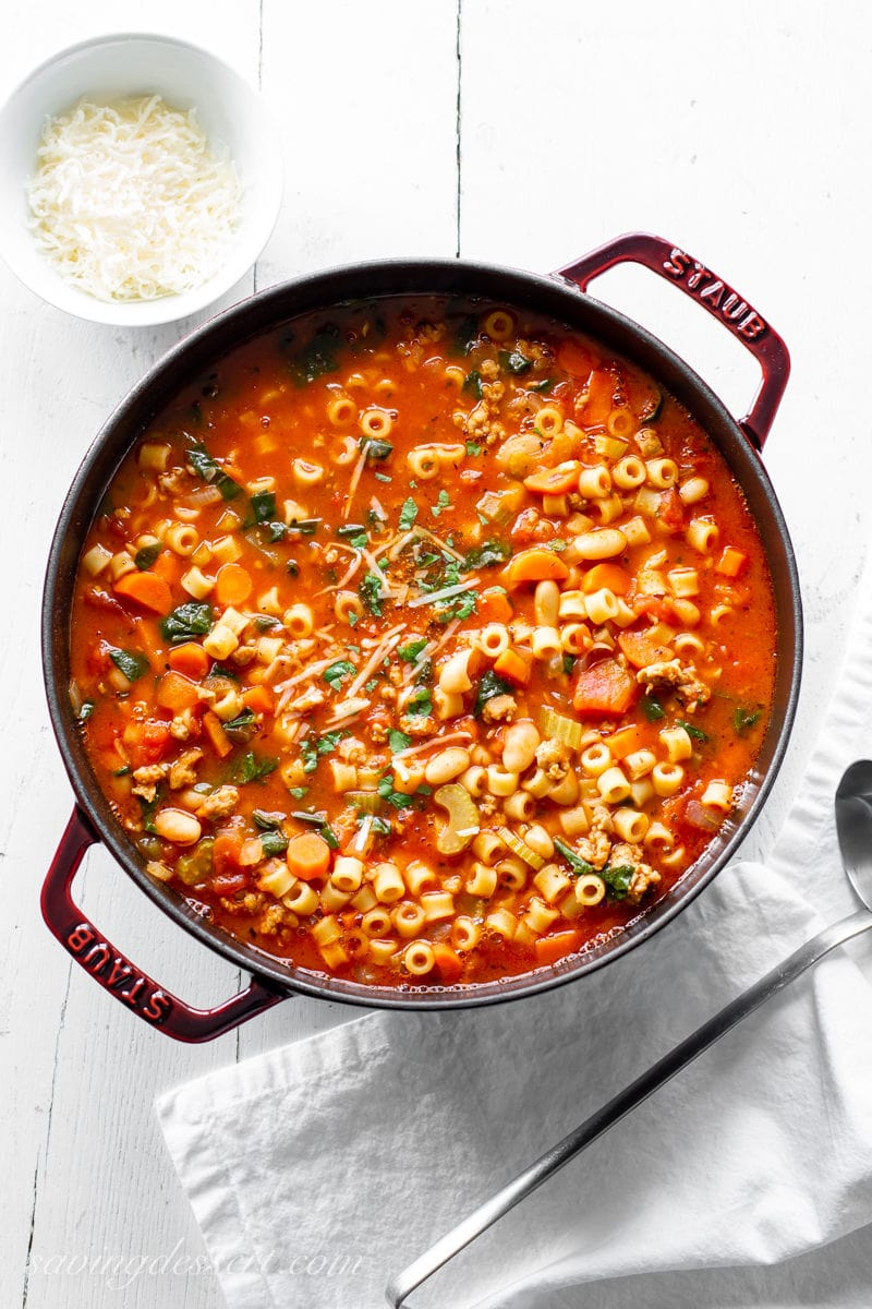 A large pot of Pasta e Fagioli soup with parsley, beans, pasta, vegetables and Italian sausage