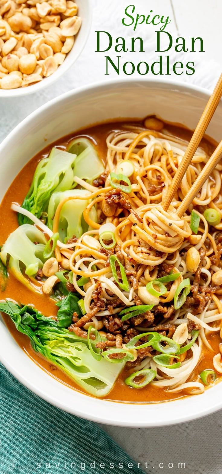 A bowl of spicy Dan Dan Noodles with bok choy and peanuts