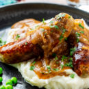 A plate of sausages with onion gravy over mashed potatoes
