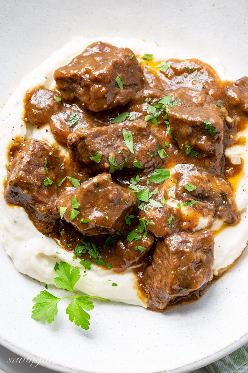 A bowl of tender Beef Tips and Gravy with mushrooms and onions served over fluffy mashed potatoes