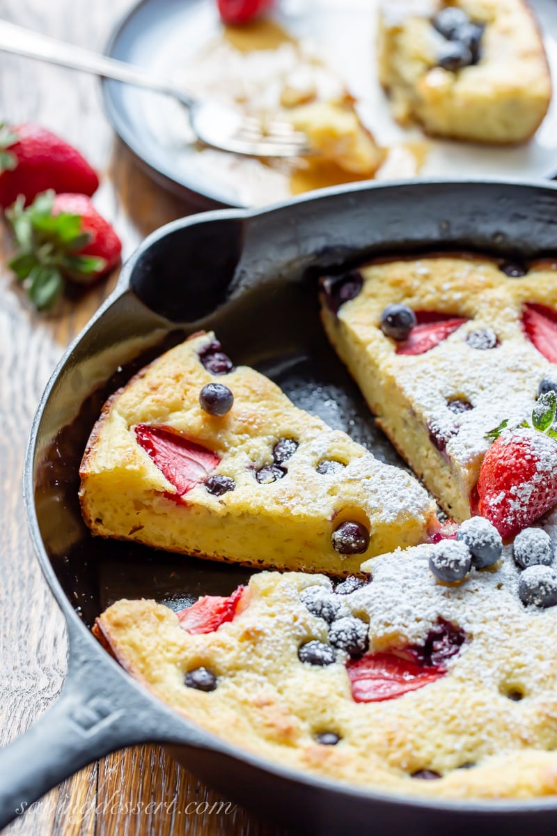 A skillet with baked pancakes topped with blueberries and strawberries