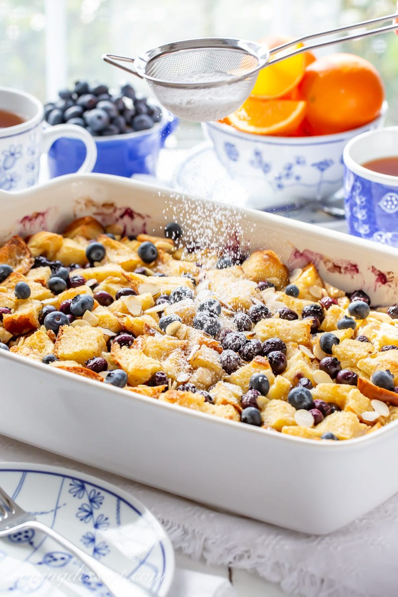 A Blueberry Overnight French Toast Casserole dusted with powdered sugar