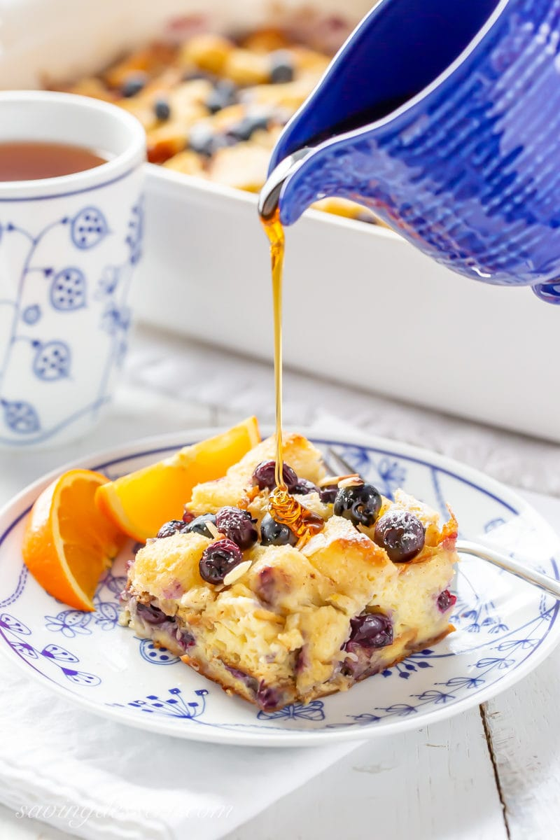 A piece of Blueberry Overnight French Toast Casserole being drizzled with maple syrup