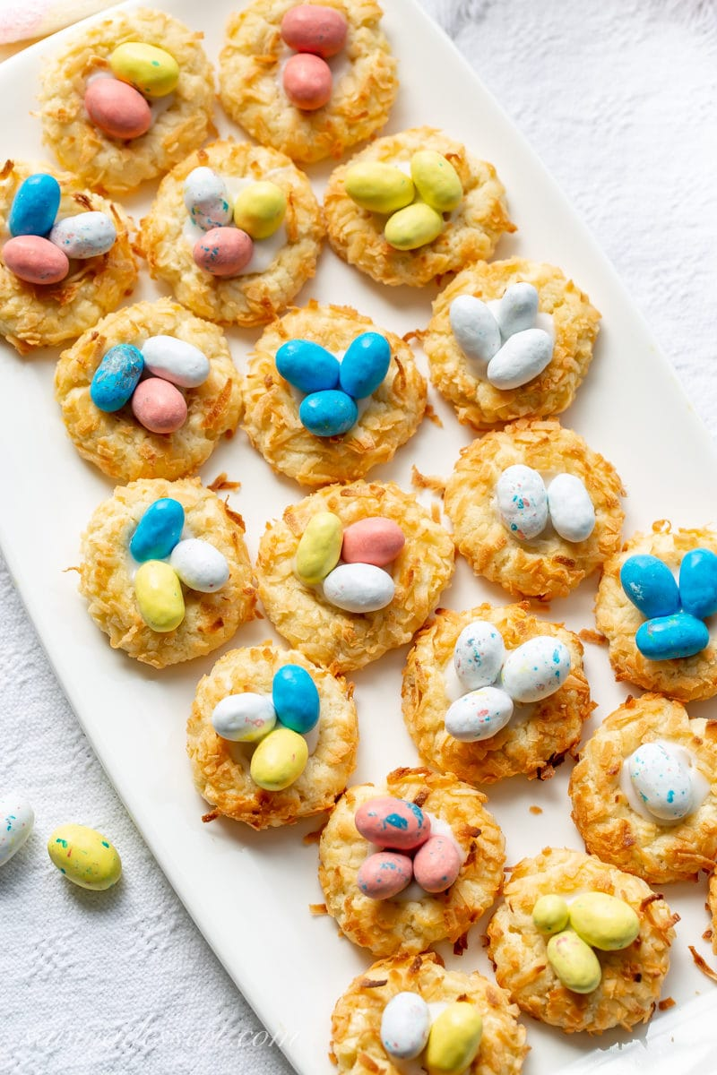 A plate of Coconut Thumbprint Cookies with speckled candy eggs in the middle