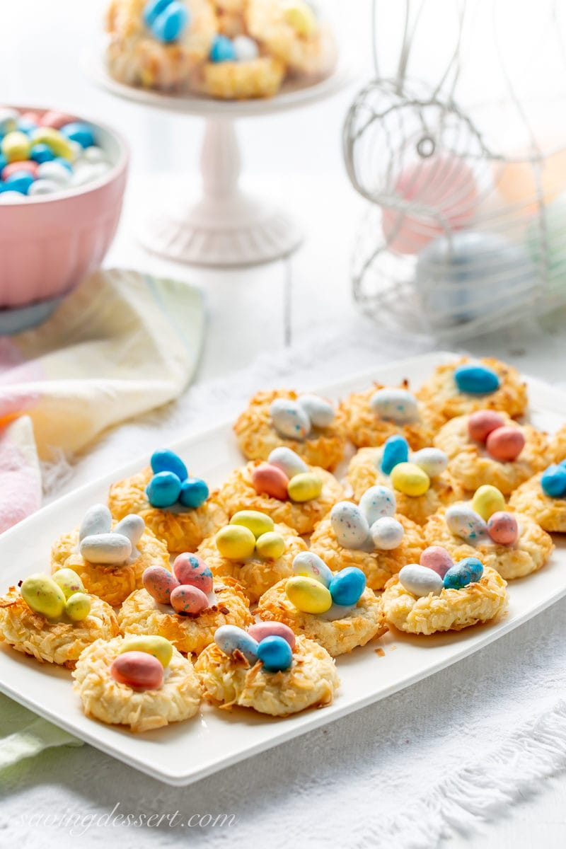 a tray of coconut thumbprint cookies with speckled candy eggs in the middle