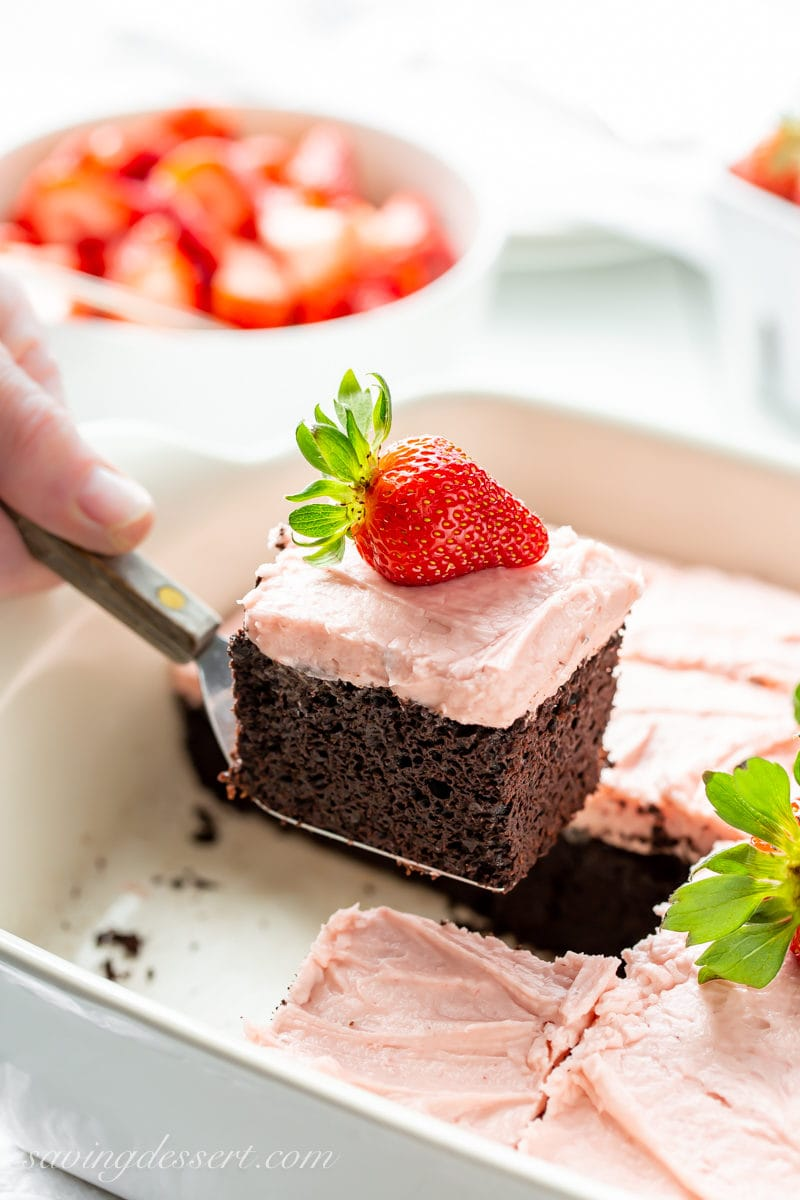A slice of dark chocolate cake with strawberry frosting and fresh strawberries